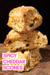 """stack of 3 cheddar jalapeño scones with a text overlay that reads """"spicy cheddar scones"""""""