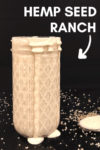 "small jar of hemp seed ranch with dressing spilling over and a spoon of dressing off to the side surrounded by spices and hemp seeds on a black background with a text overlay that reads ""hemp seed ranch"" and an arrow pointing toward the dressing"
