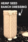 "small jar of hemp seed ranch with dressing spilling over and a spoon of dressing off to the side surrounded by spices and hemp seeds on a black background with a text overlay that reads ""hemp seed ranch dressing"" and an arrow pointing toward the dressing"