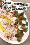 """white bean hummus on a tray surrounded by tofu feta, parsley, tomato, and olives with a text overlay that reads """"great northern bean hummus"""""""