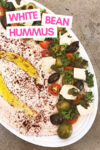 """white bean hummus on a tray surrounded by tofu feta, parsley, tomato, and olives with a text overlay that reads """"white bean hummus"""""""