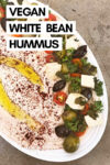 """white bean hummus on a tray surrounded by tofu feta, parsley, tomato, and olives with a text overlay that reads """"vegan white bean hummus"""""""