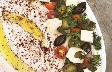 white bean hummus on a plate surrounded by olives, tomatoes, marinated tofu feta, parsley, with sprinkled olive oil and sumac on top