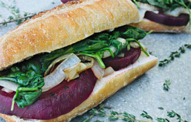 beet french dip sandwich surrounded by thyme sprigs