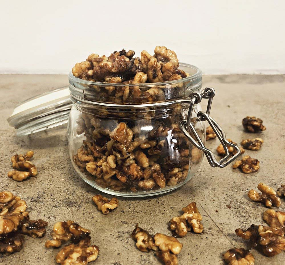 profile side shot of a jar of clove candied walnuts with surrounded by loose walnut pieces