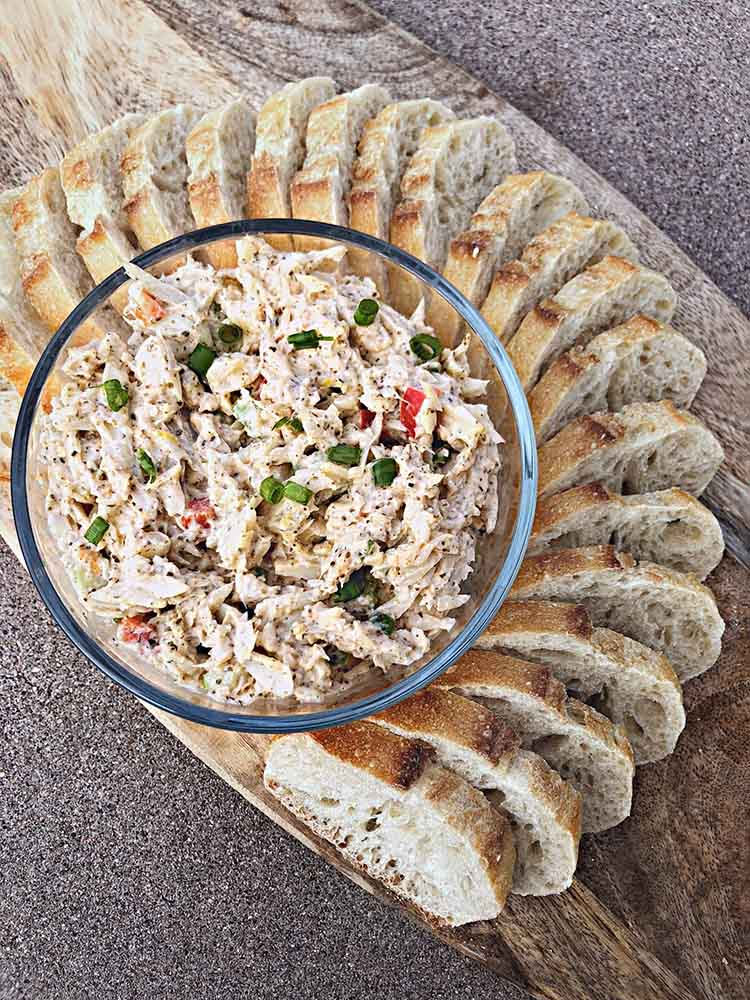overhead shot of a bowl of crab salad with french baguette slices