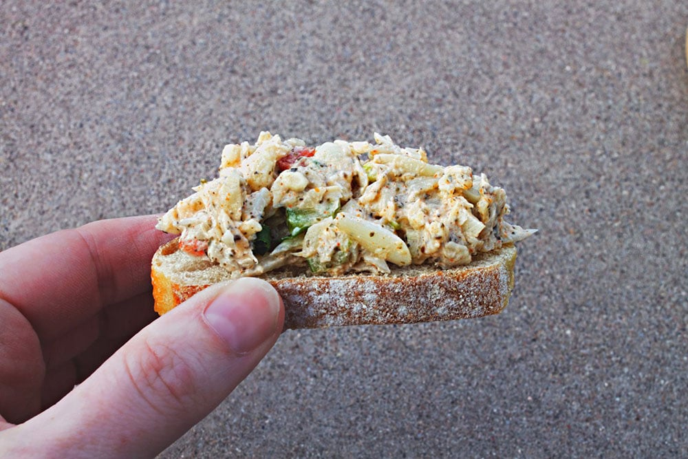 a hand holding vegan crab salad on top of a french baguette slice