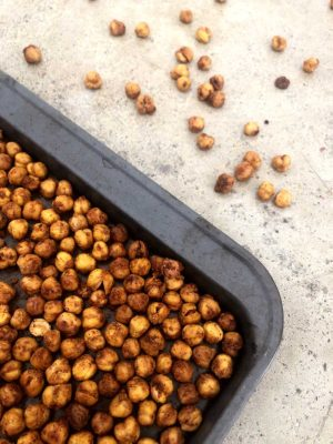 buffalo spiced crunchy chickpeas on a baking sheet with some of the chickpeas scattered across the background