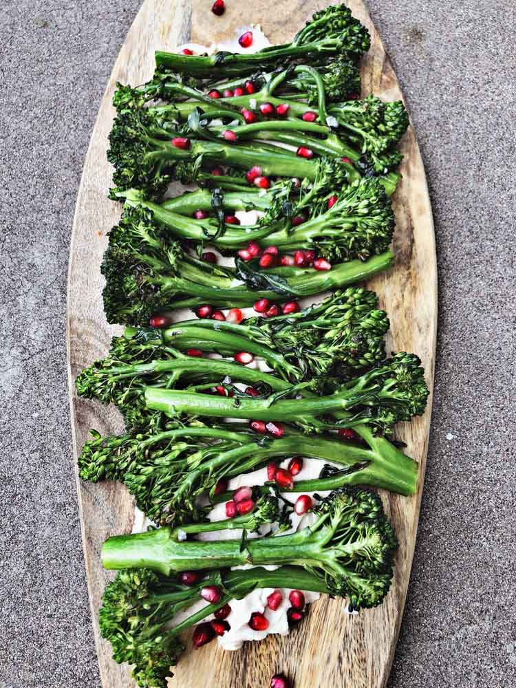 broccolini with white bean hummus and pomegranate served on a large wooden board