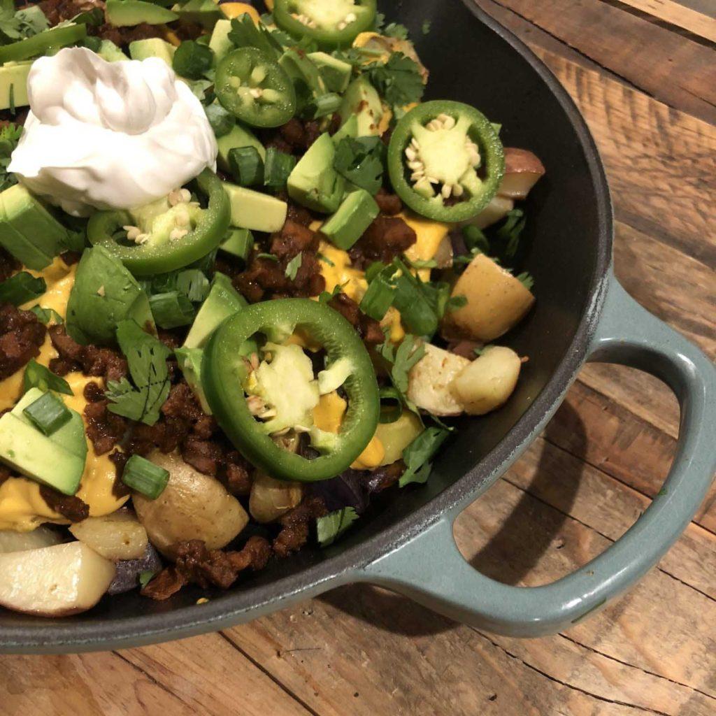 Roasted potatoes with cashew cheese, seitan chorizo, avocado, scallion, pickled jalapeños, cilantro, & vegan sour cream in a skillet