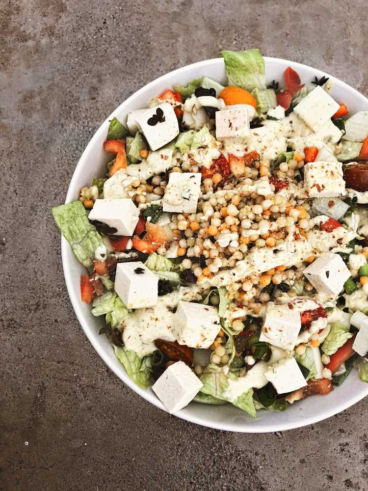 mediterranean dill salad with romaine lettuce, marinated tofu, herbed couscous, snacking tomatoes, red bell pepper, kalamata olives, hearts of palm, almond parmesan, and creamy lemon dill dressing