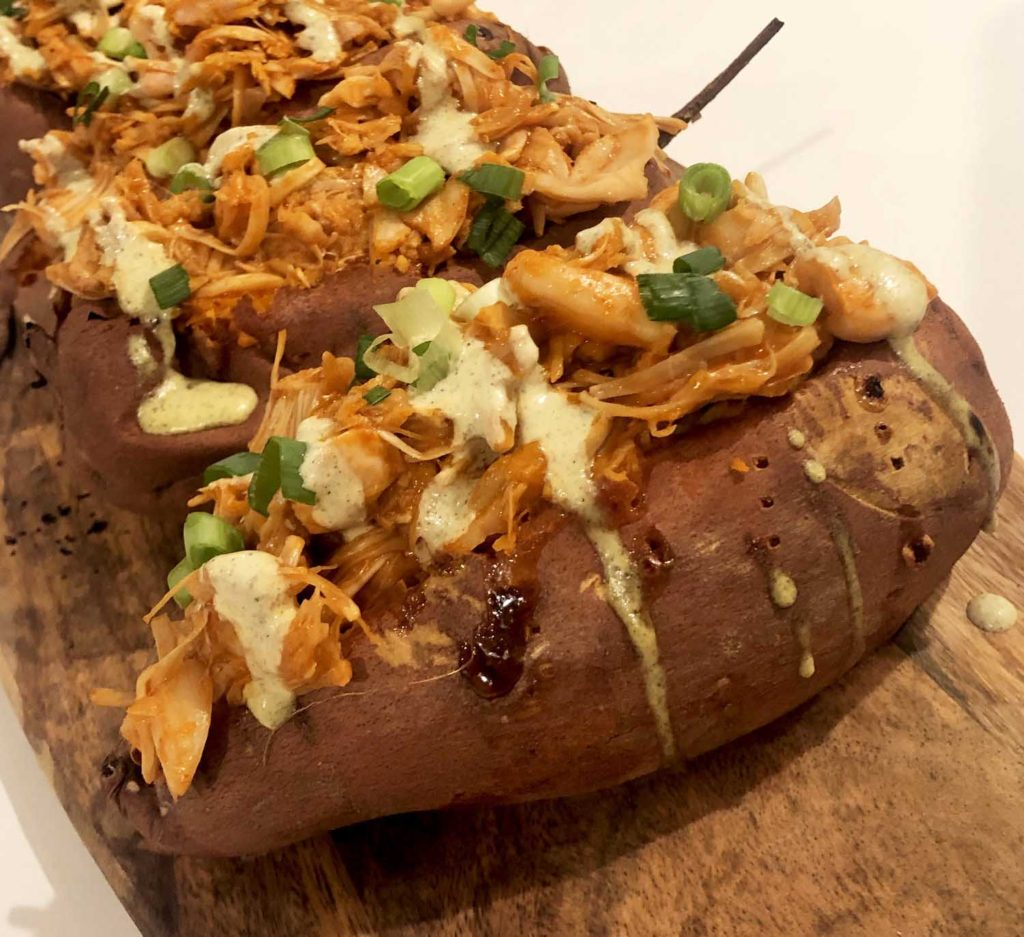 buffalo jackfruit sweet potatoes topped with hemp seed ranch and green onions