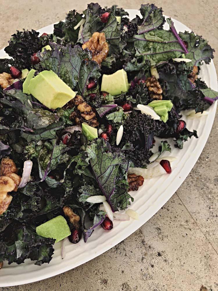 winter kale salad with purple kale, clove candied walnuts, orzo, shallot, avocado, pomegranate, and oj champagne vinaigrette