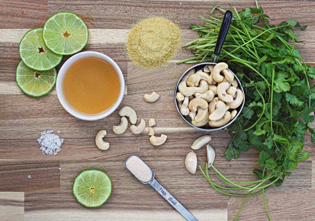 ingredient spread for cilantro lime dressing featuring limes, salt, apple cider vinegar, onion powder, garlic cloves, nutritional yeast, cilantro, and raw cashews