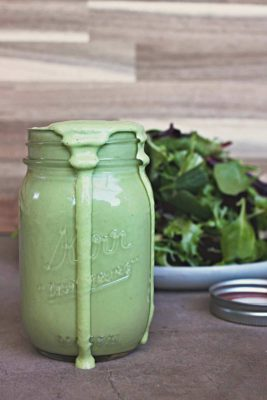 jar of creamy cilantro lime dressing with the edges overflowing and dressing dripping off to the side with a green salad in the background