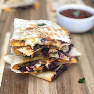 a stack of hibiscus quesadillas with salsa in the background
