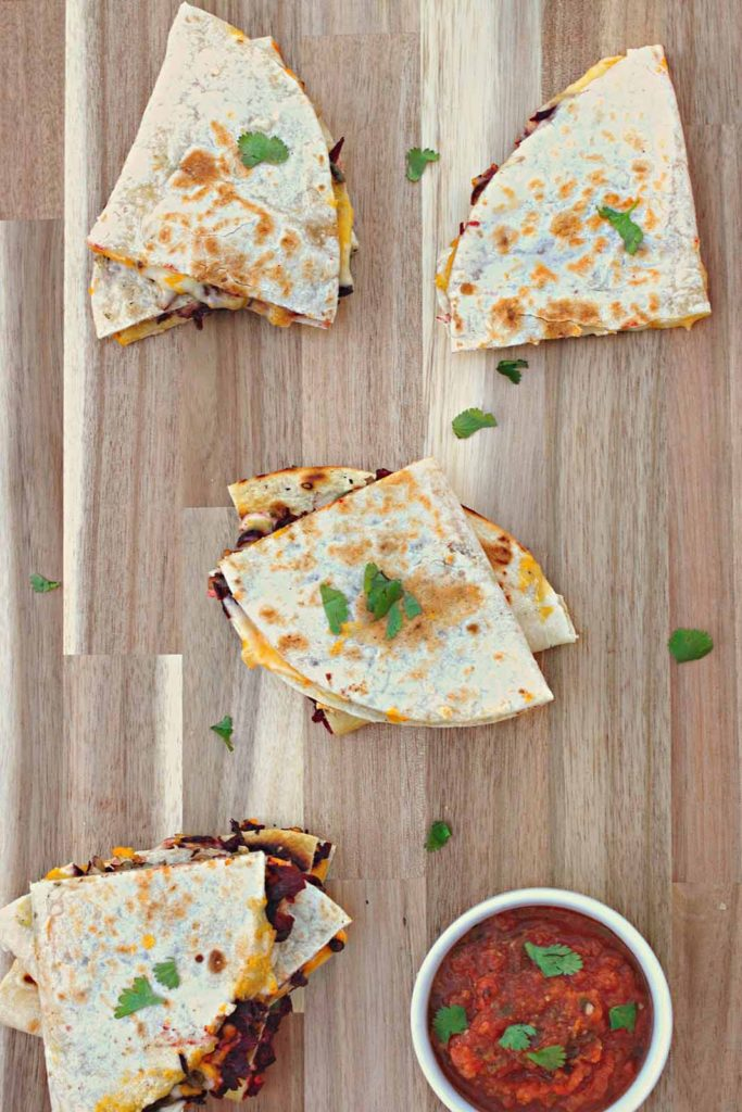 hibiscus quesadillas and cilantro scattered across a cutting board with a side of fresh salsa