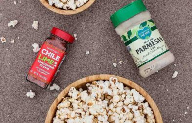 elote popcorn in three bowls displayed with follow your heart parmesan, trader joe's chili lime seasoning, and sliced lime wheels