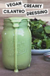 """overflowing jar of cashew cilantro lime dressing with a plate of greens behind it and a text overlay that reads """"vegan creamy cilantro dressing"""""""
