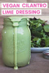 """overflowing jar of cashew cilantro lime dressing with a plate of greens behind it and a text overlay that reads """"vegan cilantro lime dressing"""""""