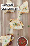 """hibiscus quesadillas on a wooden cutting board with a side of salsa and a text overlay that reads """"hibiscus quesadillas"""""""