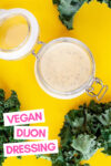 """jar of almond dijon dressing surrounded by kale leaves and a text overlay that reads """"vegan dijon dressing"""""""
