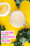 """jar of almond dijon dressing surrounded by kale leaves and a text overlay that reads """"almond dressing recipe"""""""
