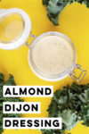 """overhead shot of a jar of almond dijon dressing against a yellow background surrounded by kale leaves and a text overlay that reads """"almond dijon dressing"""""""
