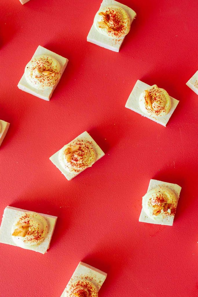 array of deviled tofu pieces on a red background