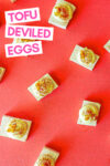 """deviled tofu eggs spread across a red background with a text overlay that reads """"tofu deviled eggs"""""""