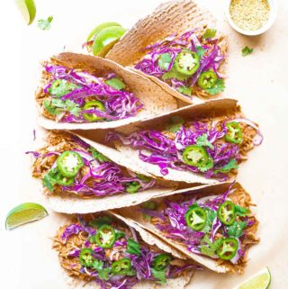 vertical stack of tacos with lime wedges, hemp hearts, and nutritional yeast