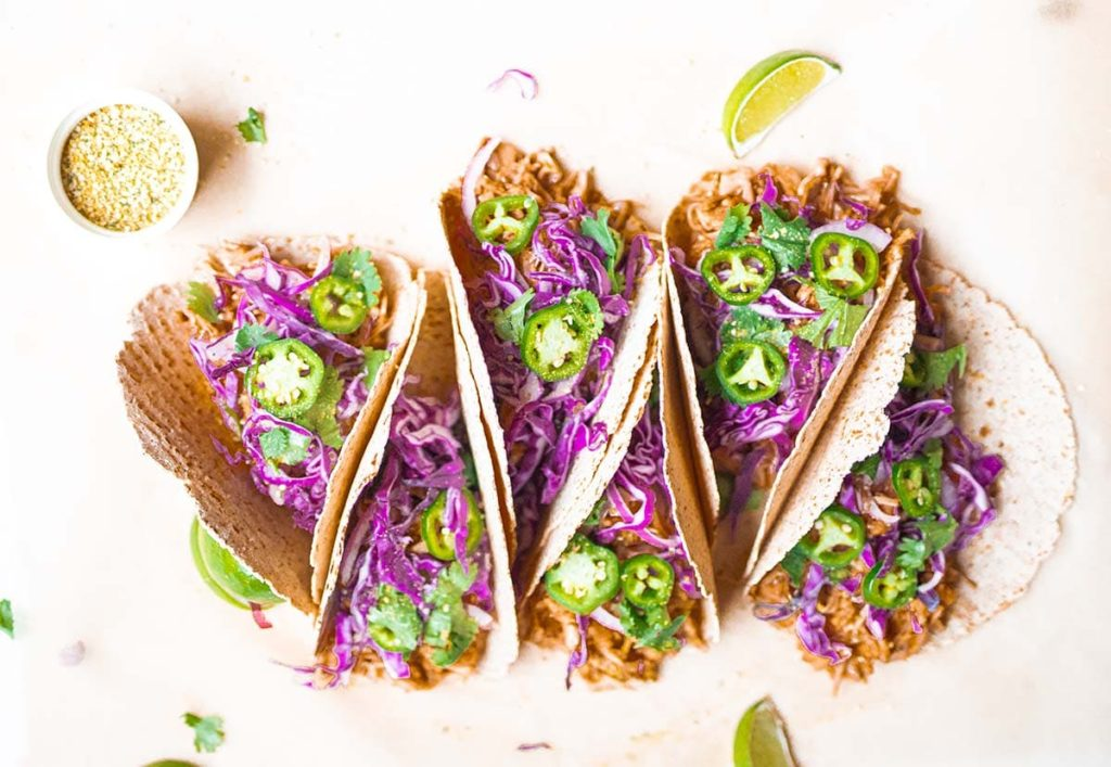 stacked jackfruit tacos with lime wedges and nutritional yeast and hemp hearts