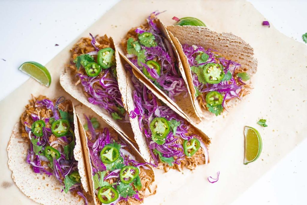 6 jackfruit tacos stacked at an angle with lime wedges