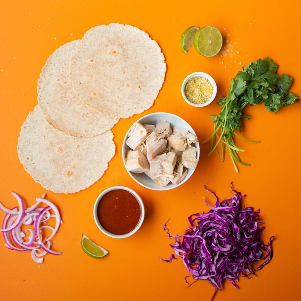 ingredient spread of low carb tortillas, red onion, lime wedges, hemp hearts and nutritional yeast, red cabbage, bbq sauce, jackfruit and cilantro.
