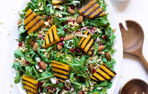 Butternut Squash Salad featuring grilled butternut squash, riced tempeh, shallot, pomegranate, almond, and an apple cider vinaigrette.