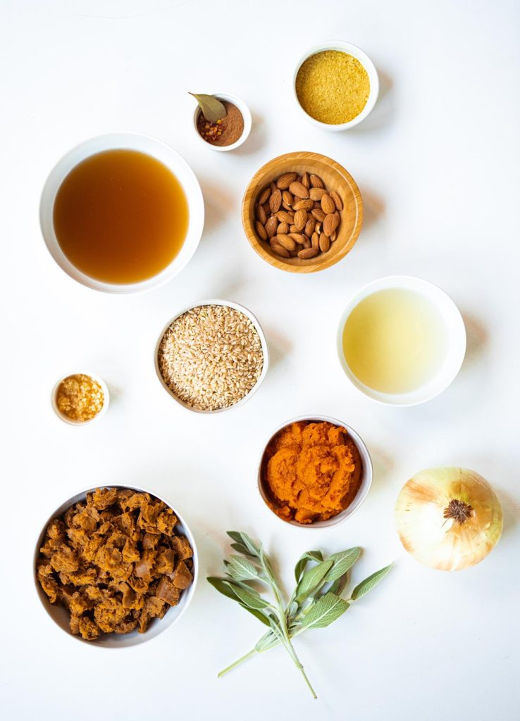 ingredient spread for pumpkin risotto with brown rice, vegetable broth, canned pumpkin, white wine, onion, vegan sausage, fresh sage, nutritional yeast, garlic, and spices.
