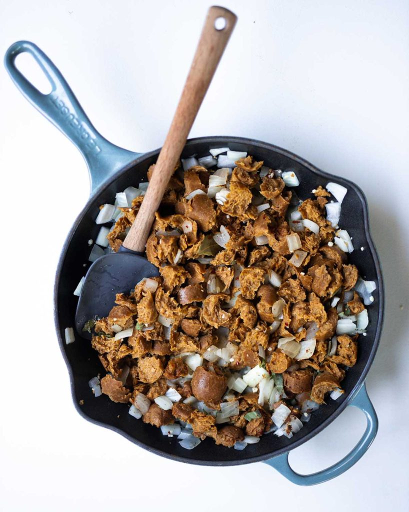 skillet filled with Tofurky sausage pieces, garlic, onion, and spices