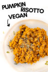"""a plate of vegan pumpkin risotto with a text overlay that reads """"pumpkin risotto vegan"""" and an arrow pointing toward the plate"""