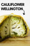 "pesto cauliflower wellington with a quarter cut out and a text overlay that reads ""cauliflower wellington"" with an arrow pointing toward the wellinton"