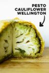 "vegan pesto cauliflower wellington with text overlay that reads ""pesto cauliflower wellington"" with an arrow pointing toward the dish"