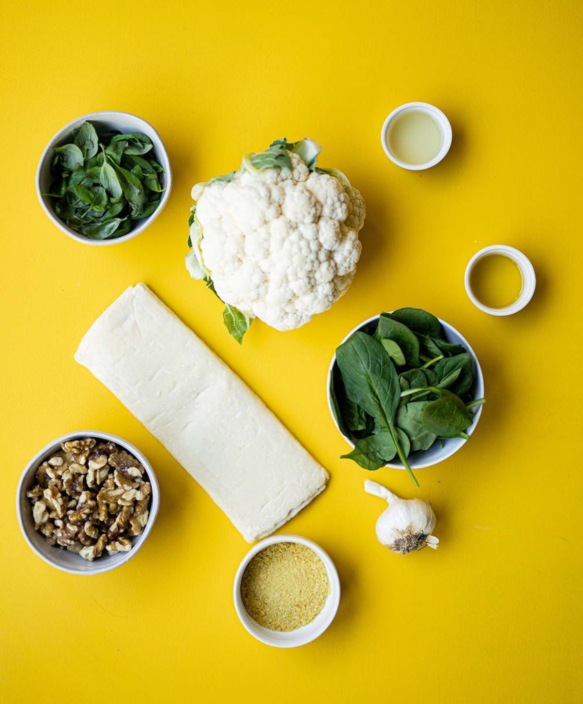ingredient spread for cauliflower wellinton featuring cauliflower, puff pastry, basil, spinach, walnuts, garlic, nutritional yeast, lemon juice and olive oil.