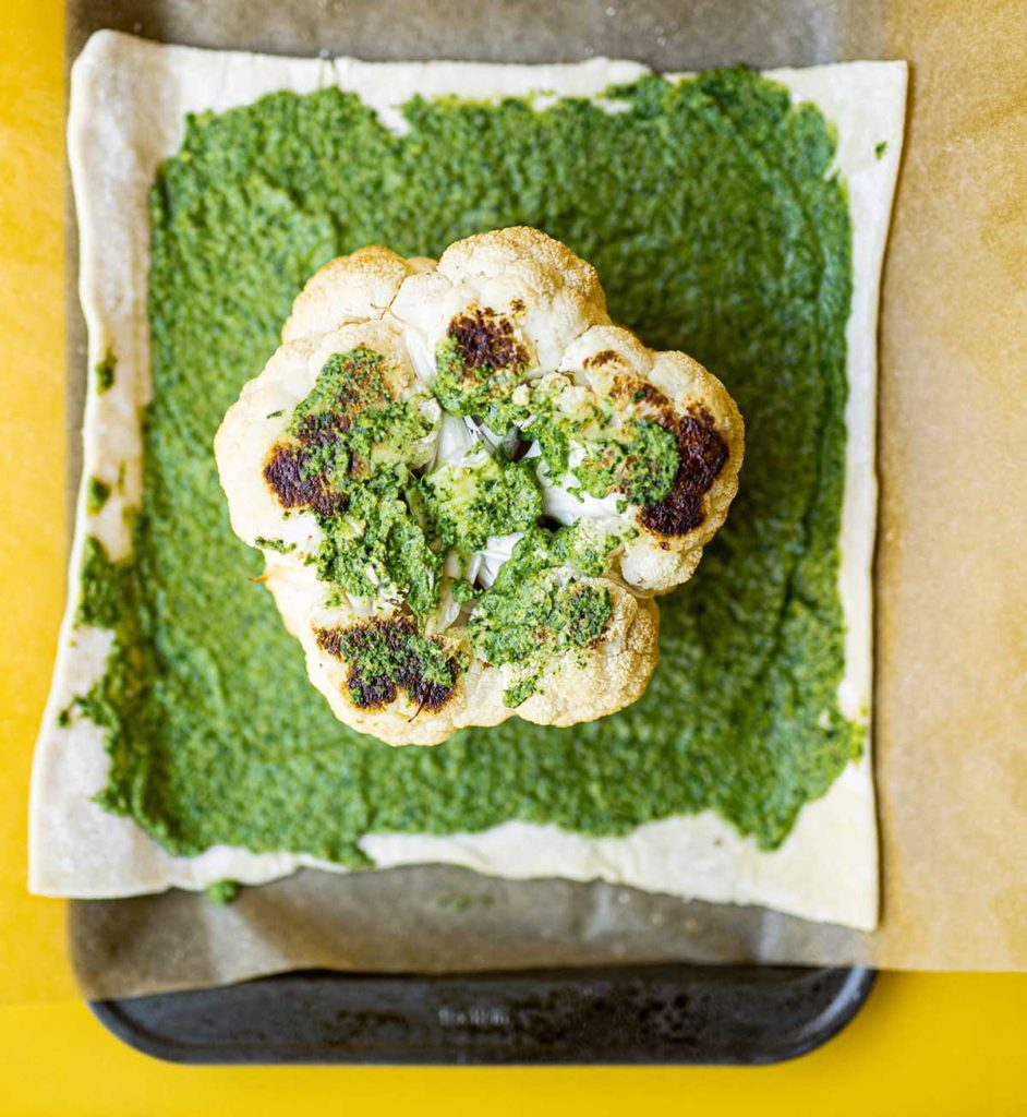 cauliflower on top of a puff pastry sheet slathered in pesto