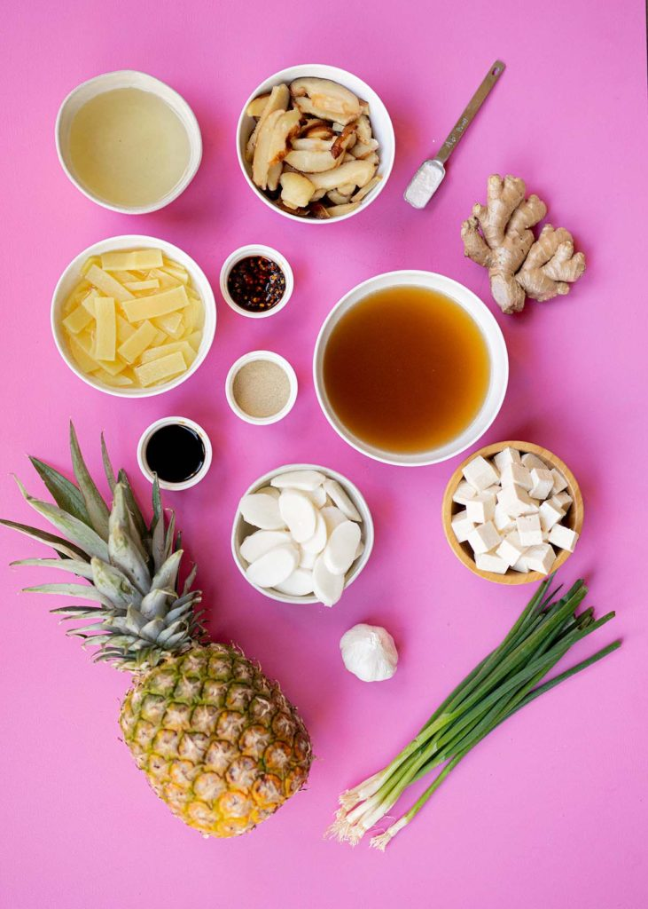 hot and sour soup ingredients: vegetable broth, rice vinegar, tofu, rice noodle cakes, ginger, garlic, white pepper, soy sauce, shiitake mushrooms, pineapple, cornstarch, chili oil, and scallions
