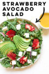 "strawberry avocado salad with arugula, vegan feta, strawberry, avocado, walnuts, and red onion and a text overlay that reads ""strawberry avocado salad"" with an arrow pointing to the plate"