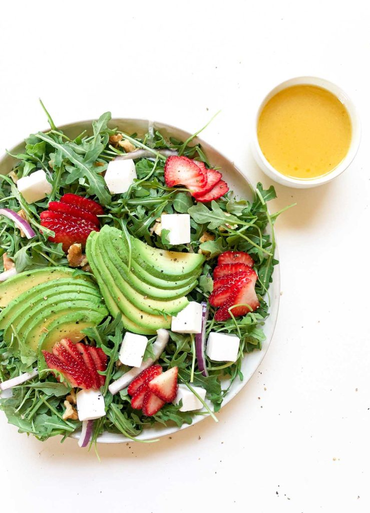 strawberry avocado salad and coconut oil dressing on a white background
