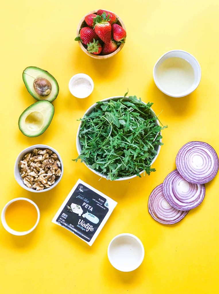 Ingredients for strawberry avocado salad: arugula, red onion, walnuts, strawberry, avocado, Violife Just Like Feta, coconut oil, orange juice, champagne vinegar and cornstarch.