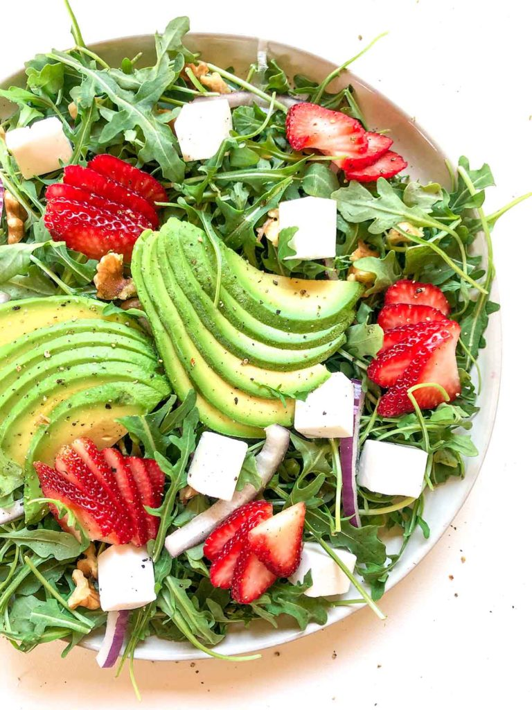 strawberry avocado salad with arugula, vegan feta, strawberry, avocado, walnuts, and red onion