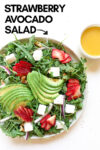 """strawberry avocado salad with a side of vinaigrette and a text overlay that reads """"strawberry avocado salad"""" with an arrow pointing toward the salad"""