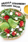 """strawberry avocado salad with a side of vinaigrette and a text overlay that reads """"arugula strawberry avocado salad"""" with an arrow pointing toward the salad"""