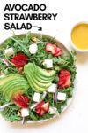 """strawberry avocado salad with a side of vinaigrette and a text overlay that reads """"avocado strawberry salad"""" with an arrow pointing toward the salad"""